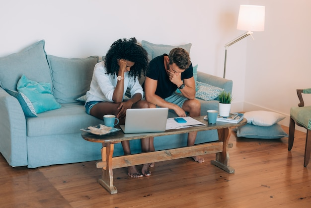 Junge zwischen verschiedenen rassen paare in der couch betonten mit den finanzproblemen, die berechnungen mit schreibarbeit tun