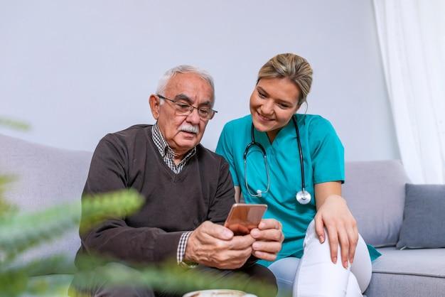 Jungekrankenschwester, die zeit mit glücklichem älterem patienten im pflegeheim verbringt