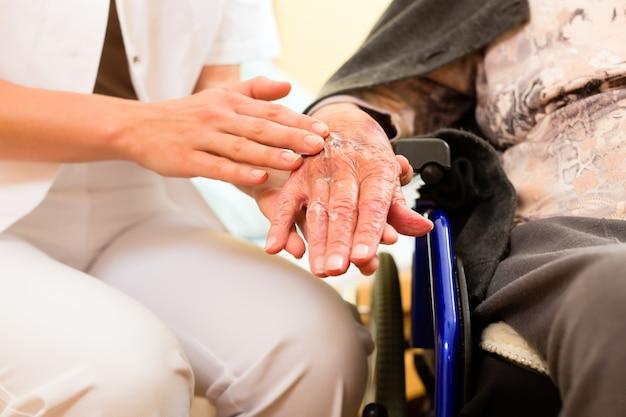Jungekrankenschwester und weiblicher senior im pflegeheim
