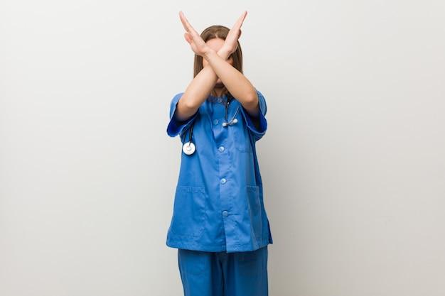 Jungekrankenschwesterfrau gegen eine weiße wand, die zwei arme gekreuzt, ablehnungskonzept hält.