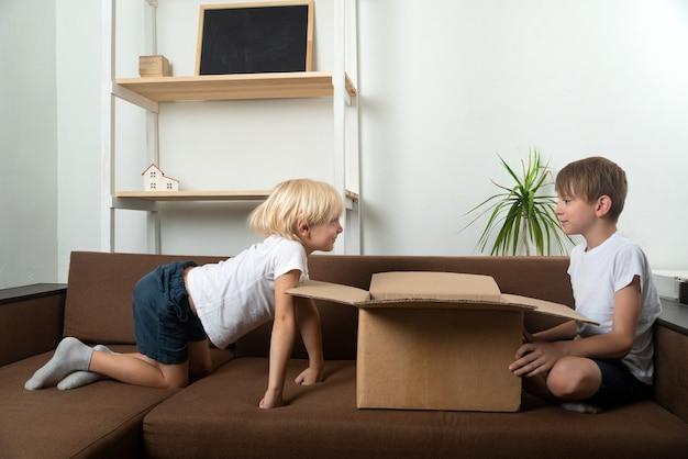 Jungen auf der couch in der nähe einer großen offenen kiste