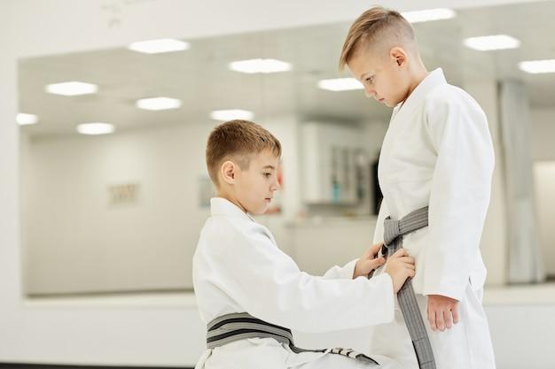 Jungen binden den gürtel am kimono