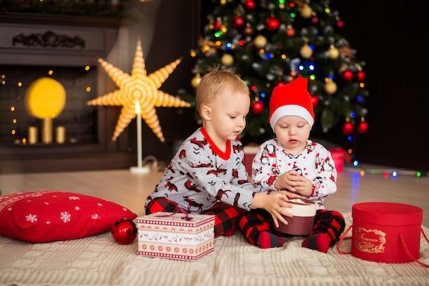 Jungen, brüder, kinder in weihnachtskostümen, pyjamas mit weihnachtsschmuck