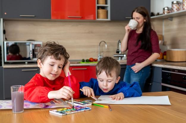 Jungen, die auf der küche zeichnen, während mutter tee oder kaffee trinkt