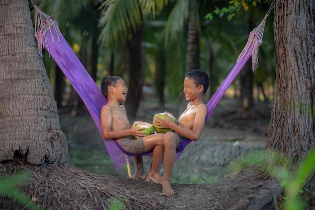Jungen, die frischen kokosnusssaft im kokosnussgarten nahe dem schwimmenden markt damnoen saduak, provinz ratchaburi fahren