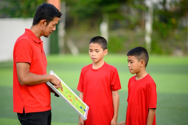 Jungen, die fußball auf dem fußballtrainingsfeld spielen