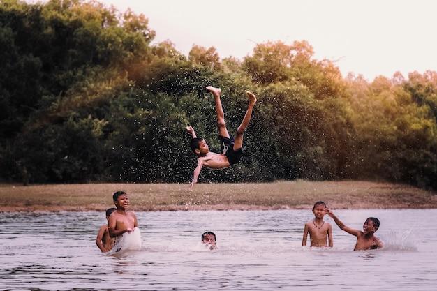 Jungen, die in den see springen.