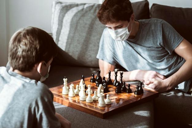 Jungen, die zu hause schach spielen, während sie unter quarantäne gestellt werden