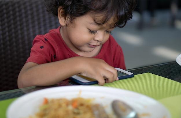 Jungen essen kein essen, weil sie smartphones spielen