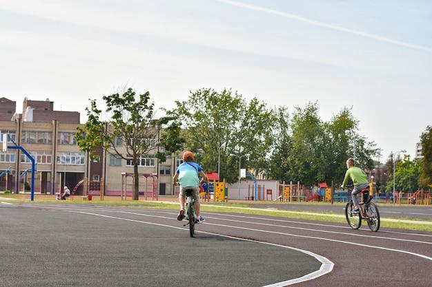 Jungen fahren fahrrad auf dem radweg eines öffentlichen stadions in der stadt