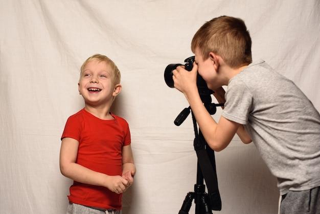 Jungen fotografieren sich gegenseitig mit einer spiegelreflexkamera. heimstudio. junge bloggerin. weiß
