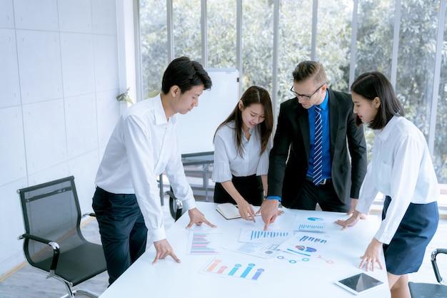 Jungen geschäftsleuten wird im besprechungszimmerbüro ein marketingarbeitsprojekt für den kunden präsentiert