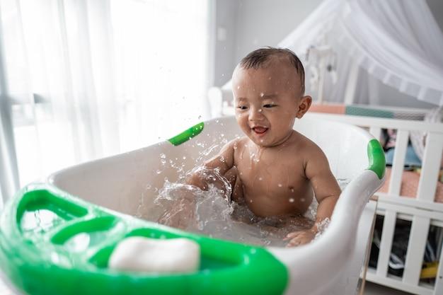 Jungen kleinkind genießen das spielen mit wasser, während sie ein bad nehmen