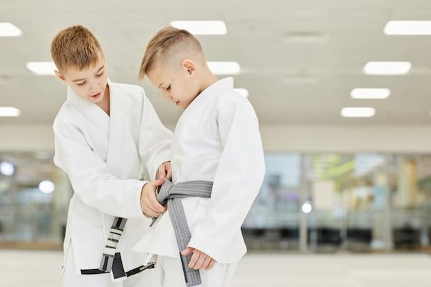 Jungen lernen, den gürtel zu binden