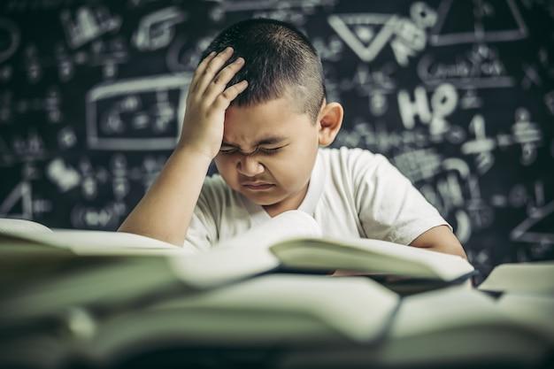 Jungen mit brille schreiben bücher und denken im klassenzimmer