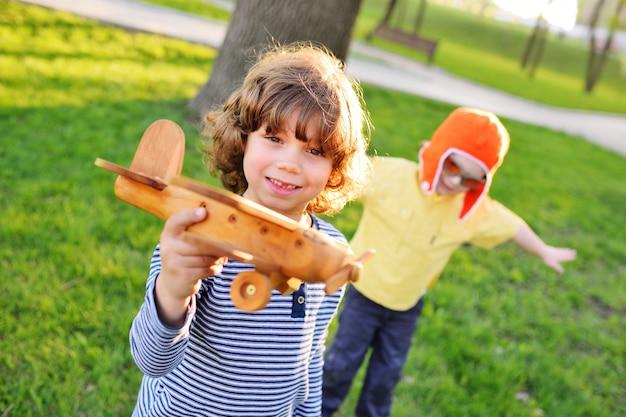Jungen mit dem lockigen haar spielen ein hölzernes spielzeugflugzeug im park.