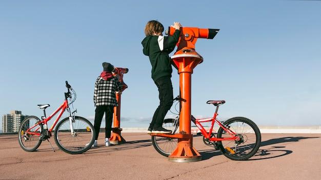 Jungen mit fahrrädern schauen durch teleskope im freien