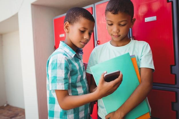 Jungen mit smartphone auf dem flur