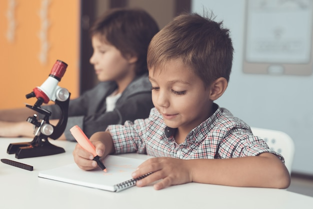 Jungen sitzen mit laptop und mikroskop zu hause.