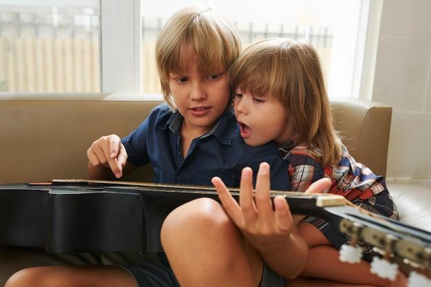 Jungen spielen akustikgitarre