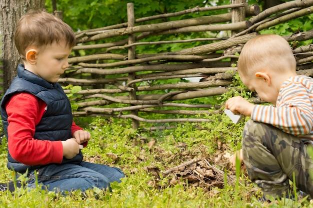 Jungen spielen mit streichhölzern, die ein kleines lagerfeuer anzünden