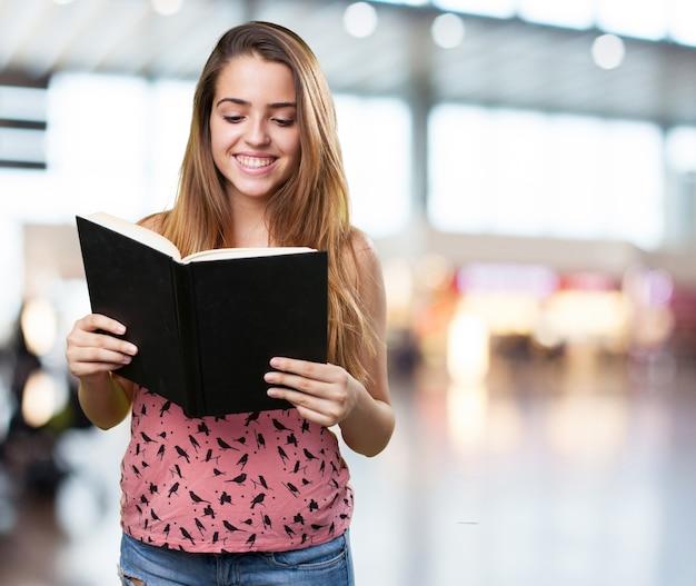 Jungen studenten ein buch auf weißem hintergrund liest
