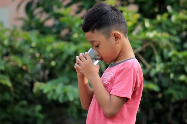 Jungen trinken wasser. wasser ist sehr gut für die gesundheit von kindern