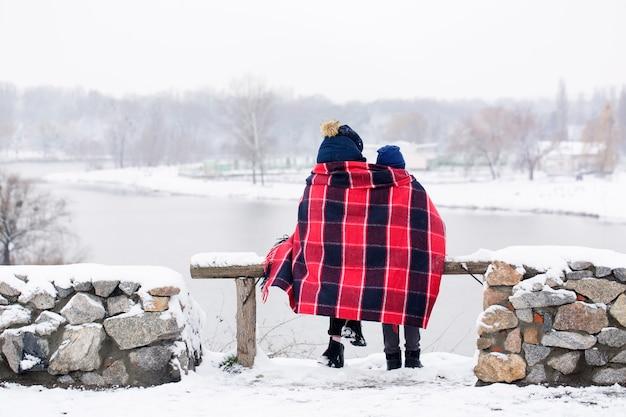 Jungen und frauen sitzen im winter in eine decke gewickelt Premium Fotos