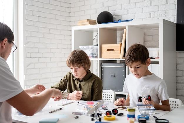 Jungen und lehrer haben spaß daran, gemeinsam in der werkstatt roboterautos zu bauen