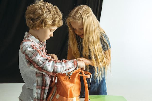 Jungen und mädchen bereiten sich nach einer langen sommerpause auf die schule vor. zurück zur schule. kleine kaukasische modelle, die eine tasche zusammen auf raum packen