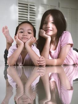 Jungen und mädchen der asiatischen geschwisterschulkinder, die während der covid-19-pandemie entspannen. kinder zu hause eingesperrt oder selbst isoliert. konzept der familienunterstützung.