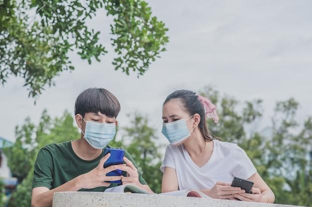 Jungen und mädchen, die mobiles smartphone für e-learning verwenden