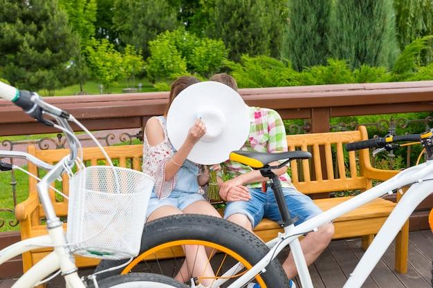Jungen und mädchen, die sich hinter dem hut küssen, während sie auf einer bank sitzen, parkten ihre fahrräder in einem park gegenüber sich selbst