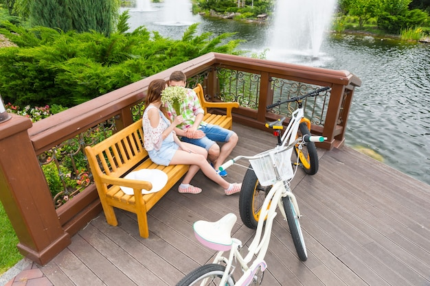 Jungen und mädchen, die sich hinter dem strauß kleiner weißer blumen küssen, während sie auf einer bank sitzen, parken ihre fahrräder in einem park gegenüber sich