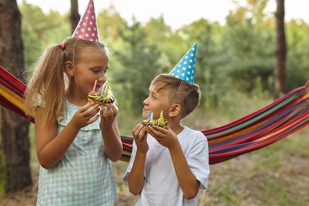 Jungen und mädchen feiern geburtstag im freien im garten