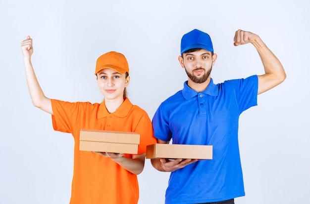 Jungen und mädchen in blauen und gelben uniformen, die mehrere pakete zum mitnehmen und ihre macht halten.