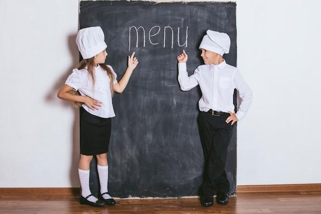 Jungen und mädchen kochen mit schieferbrett unter dem textmenü