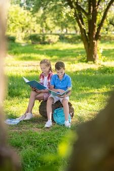 Jungen und mädchen lesen auf baumstumpf im park