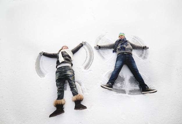 Jungen und mädchen machen schneeengel