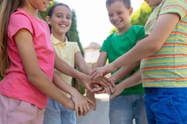 Jungen und mädchen mit ausgestreckten armen als zeichen der freundschaft