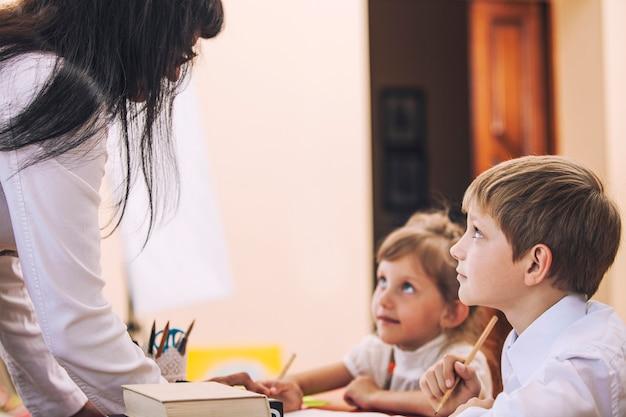 Jungen und mädchen mit dem lehrer in der schule hat eine glückliche. bildung, tag des wissens, wissenschaft, generation, vorschule, lehrertag.