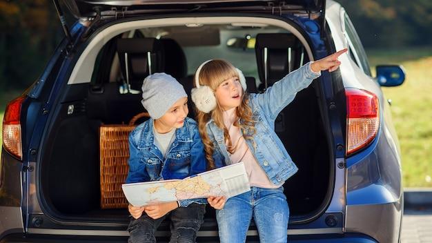 Jungen und mädchen schauen auf die straßenkarte, während sie im kofferraum des autos sitzen