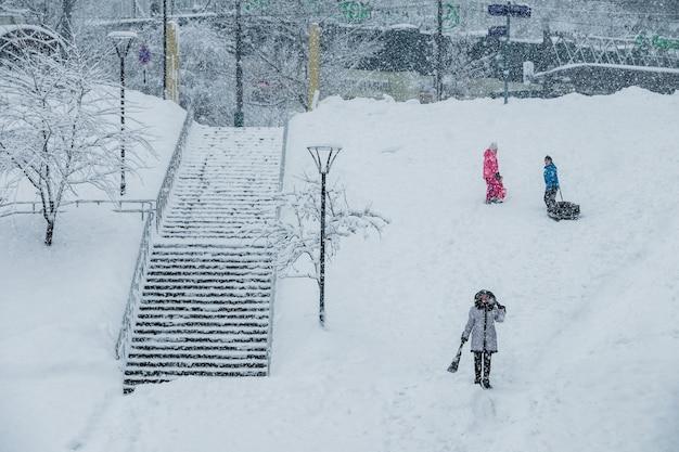 Jungen und mädchen snowtubing einen schneefall