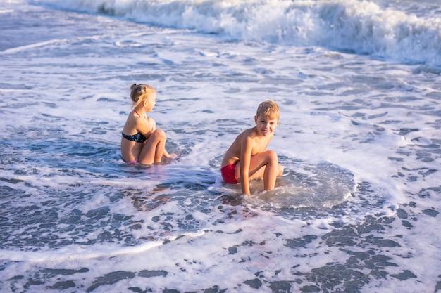 Jungen und mädchen spielen am strand in den sommerferien. kinder in der natur mit schönem meer, sand und blauem himmel.