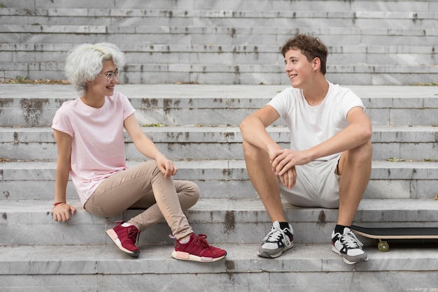 Jungen und mädchen sprechen, während sie auf der treppe sitzen