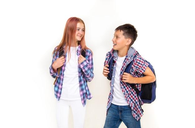 Jungen und mädchen teenager 11 jahre alt schüler und schülerin, auf weißem hintergrund mit rucksäcken und lächelnd auf einander suchen. gekleidet in kariertem hemd und weißem hemd