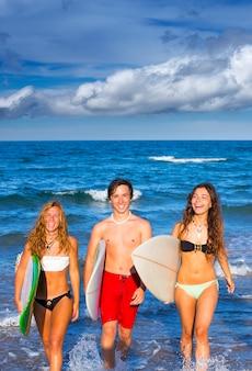 Jungen und mädchen teenager surfer kommen vom strand
