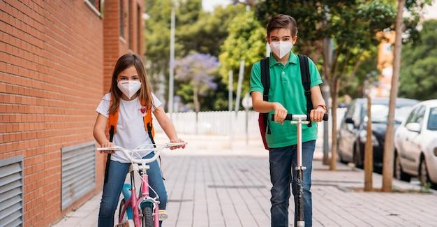 Jungen und mädchen tragen masken und fahren einen roller und ein fahrrad auf der straße