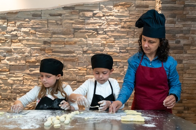 Jungen und mädchen zwillingsgeschwister, die teig mit ihrer mutter in einem kochworkshop zubereiten, der als köche verkleidet ist