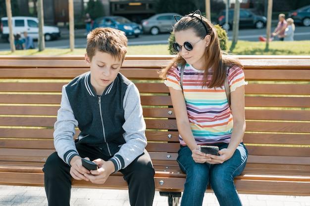 Jungen- und mädchenjugendliche, die, den smartphone betrachtend lesen